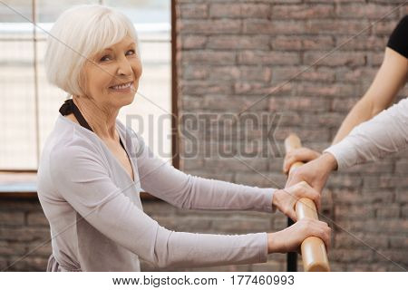 The most optimistic student ever. Cheerful capable retired woman dancing in the art studio while expressing happiness and standing near the barre