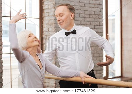 Mastering our grace . Capable elegant aging couple performing in the art studio while dancing and using barre