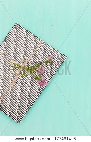 Top view on nicely wrapped gift with clover as decoration on turquoise background. Present for birthday or any other celebration. Party. Holidays concept