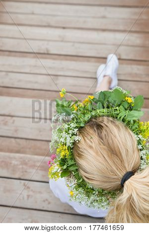 Top view on blond woman's head with wild flowers wreath. Girl with flowers sitting on wooden bridge outdoors. Countryside life. Summer and lifestyle concept.