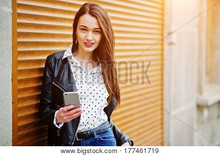 Portrait Of Stylish Young Girl Wear On Leather Jacket With Mobile Phone At Hand Background Shutter T