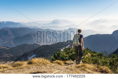 Male hiker walks relaxed on a trail on a mountain summit. Great mountain view to fog filled valleys and mountain ranges in background. Alps, Italy.