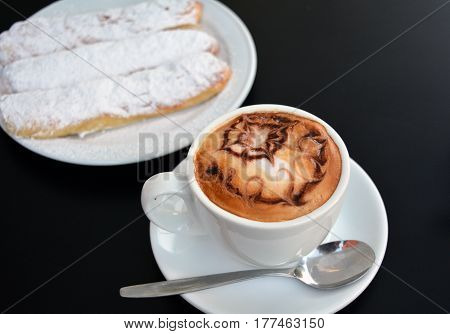 Cup of delicious foamy cappuccino with dessert on a black background.