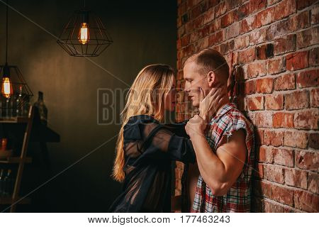 Couple looking at each other with desire standing beside wall