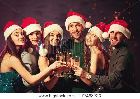 Friends clinking glasses at Christmas party in night club