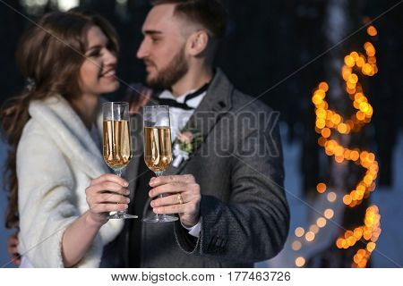 Happy wedding couple with glasses of champagne on winter evening