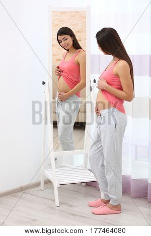 Beautiful pregnant woman looking in mirror in light room