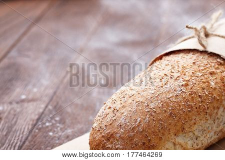 One white bread with flour on a wooden background. Advertising bread. Leaning flour. White loaf in decorative paper and rope. Brown table.