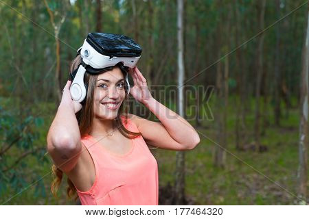 beautiful woman with virtual reality in outdoor park. VR headset glasses device.