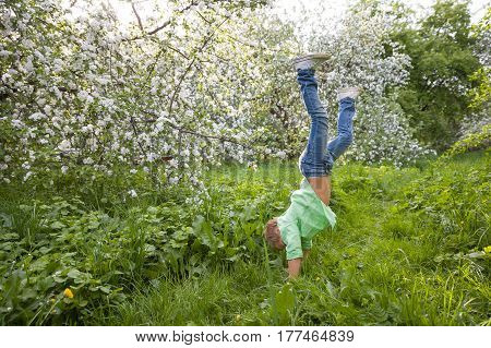 Happy kid boy standing upside down and having fun in the summer grass. Funny boy standing on his head. Active and healthy lifestyle concept.