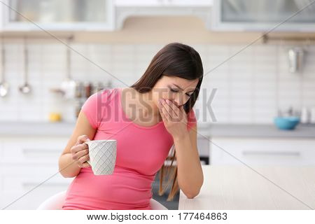 Beautiful woman experiencing signs of pregnancy in kitchen
