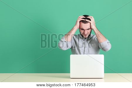 Handsome young man suffering from headache while working with laptop, on color background