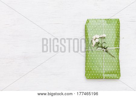 Top view on nice wrapped gift with flowers on white wooden background. Present for birthday Christmas and any other celebration. Holidays concept
