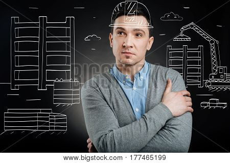 Responsible work. Concentrated construction engineer standing on the area of construction set and planning his work