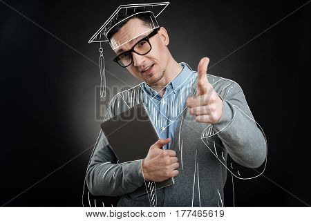 Great result. Pleasant successful graduate holding textbook and pointing you while enjoying his graduation celebration
