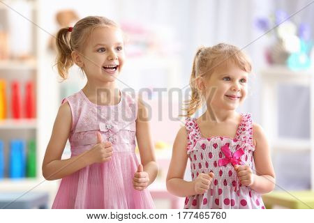Cheerful little girls playing at home