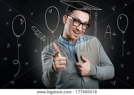 Successful graduate. Cheerful delighted student holdign textbook and smiling while enjoying his graduation ceremony poster