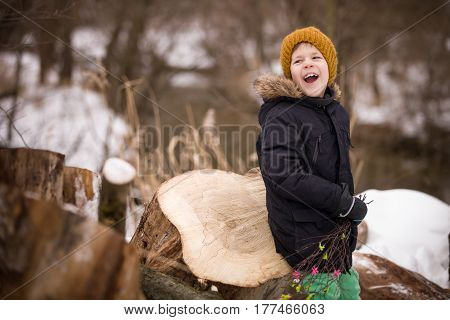 Cute laughing kid boy sitting on old tree stump in the park. Child having fun outdoors. Winter and lifestyle concept