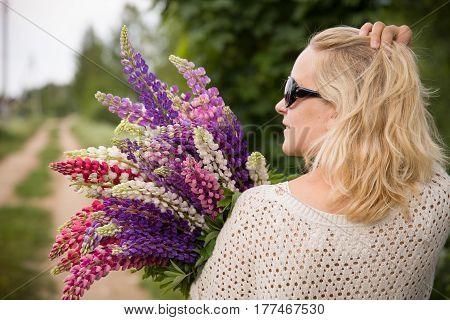 Smiling young girl holding a bunch of beautiful lupine flowers. Purple and pink lupin bouquet. Woman with bouquet of wild lupin flowers on sunny summer field.