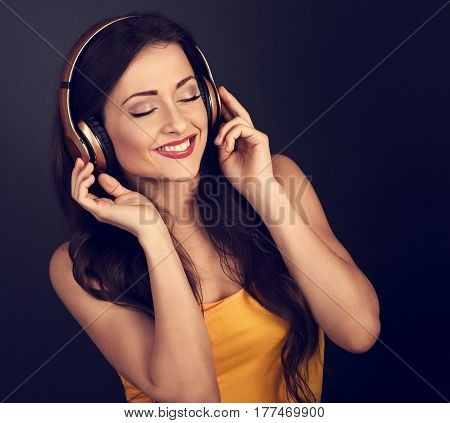 Beautiful Calm Young Woman In Yellow Top Listening The Music In Wireless Headphone With Closed Eyes