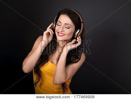 Beautiful Calm Young Woman In Yellow Top Listening The Music In Wireless Headphone With Closeud Eyes
