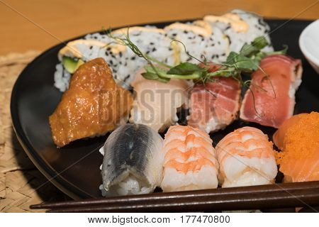 Closeup of a sushi meal on a black plate