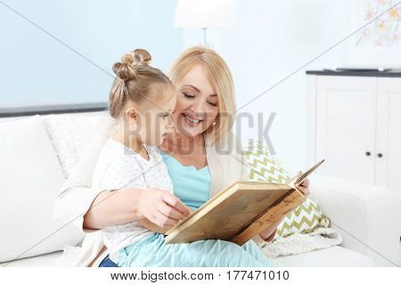 Grandmother looking at photo album with her grandchild