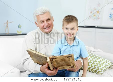 Grandfather looking at photo album with his grandchild