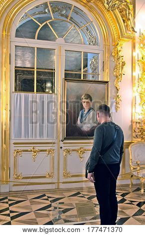 TSARSKOYE SELO, SAINT-PETERSBURG, RUSSIA -- FEBRUARY 14, 2016: Man looks at the portrait of Alexei Nikolaevich Romanov, Tsarevich of Russia in The First Antechamber of The Catherine Palace