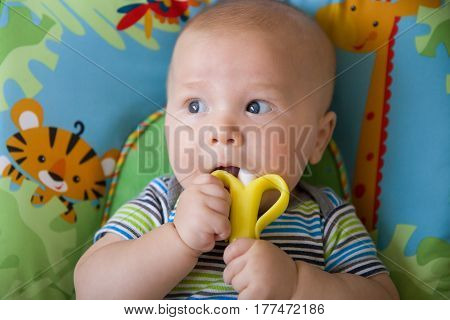 Adorable baby less than a year old playing with teething toy banana. top view on laying baby boy using teething banana toy. Child's first teeth.