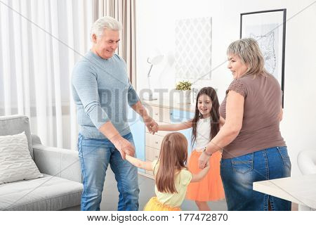 Grandparents with granddaughters dancing in the room