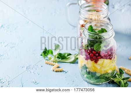 Variety of salads in mason jars. Fruit salad mango, pomegranate, greens, vegetables, wholegrain pasta, carrots and cauliflower, salmon. Standing over blue texture background. Food to go. With space