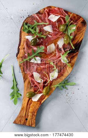 Beef carpaccio on olive wood serving board with capers, olive oil cheese and arugula, served over blue stone texture background. Top view with space for text.