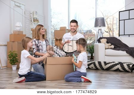 Happy family unpacking cardboard box on floor in new house