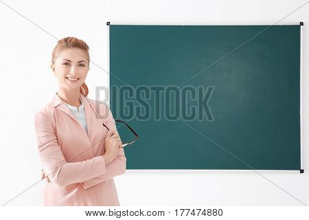 Young teacher beside blackboard on white background