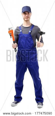 Young plumber holding pipe wrench and plunger on white background