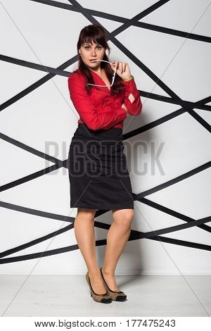 Young business woman dressed in red shirt and black skirt with glasses