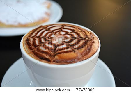 Cup of delicious foamy cappuccino on a black background.