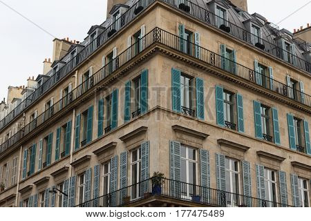 A corner of a building. Windows with shutters