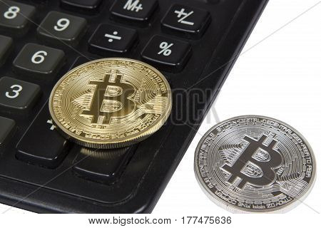 gold and silver bitcoin lies on a black calculator. electronic money and cryptocurrency