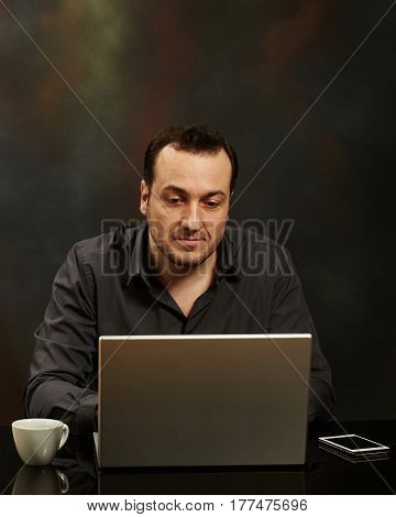 Businessman working on a laptop on a black table.