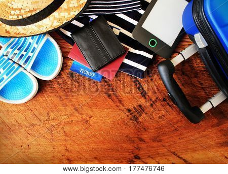 Suitcase and tourist stuff on wooden background. Top view. Free text space.