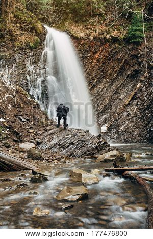photographer photographing rock waterfall in the mountains