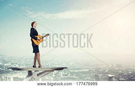Hand of waiter presenting on tray woman playing guitar