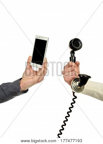 Man's hand holding a mobile phone and woman's hand holding a speaker of a vintage telephone.Technological evolution.