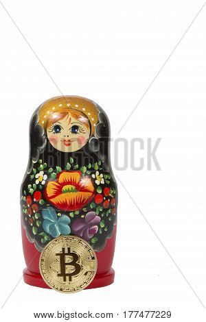 matryoshka and gold bitcoin on a white background. electronic money and cryptocurrency