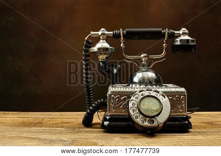 Vintage silver  telephone on a  wooden table.