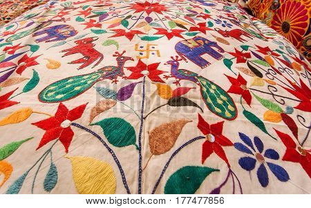 Beautiful birds and animals on surface of vintage textile colorful bedspread. Old asian market design