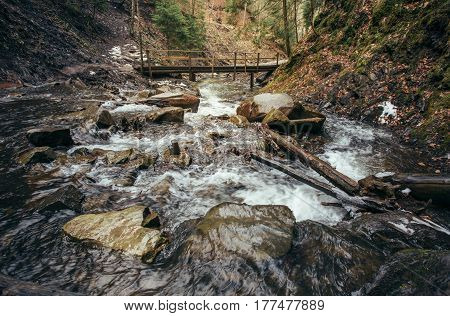 rocky Fast mountain river and wooden bridge