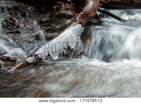 fast flow of water in river cascade with ice parts